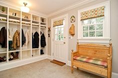Built-in white storage lockers, cream walls, white trim and beige stone tiles. Rustic wooden bench with plaid cushion beneath window. Key holder and mail holder on either side of the door.