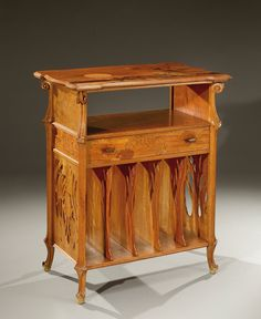 A carved walnut music shelf with exotic wood marquetry, and a border of notes of music and birds admiring the sunset. Vertical compartments for music scores are on the lower part. Signed «Gallé». Circa 1900.