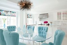 Suzie: Fawn Galli Interiors - Baby blue tufted dining chairs, oval 1970s lucite dining table, ...