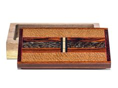 Handmade box by Jeffrey Seaton with a lid of black palm, cocobolo, ebony, maple, walnut, satine, leapardwood. The body is made from walnut and is 1 1/2″D. Each box is completely handmade using rare and exotic woods. Each is created spontaneously and no two are ever exactly alike. Each is sanded seven times to a satin smooth surface and finished in an oil and wax finish. Size: 9 1/2″L x 5 5/8″D x 2 1/2″H Price: $325.00  -- on ScrimshawGallery.com #woodworking #jewelrybox