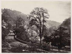 Anonymous | Panoramisch uitzicht op huizen en een weg tegen een heuvelrug in Matlock, Anonymous, 1878 - 1890 | Onderdeel van Reisalbum Europese steden, vermoedelijk Zweeds.