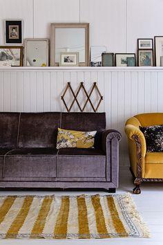 Aubergine sofa. Mustard Armchair. Mustard & white striped rug. White wood panelled wall.