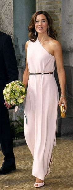 Crown Princess Mary of Denmark in a stunning full length off-the-shoulder blush pink gown, which she matched with a delicate pair of pointed peep-toe heals of the same color. She carried a sparkling gold sequined clutch purse, wore a long pair of diamond earrings which added an extra touch of glamour. She accessorize with a thin gold necklace and matching gold bracelets. Her taught waist was accentuated by a thin gold belt while her dress's diagonal lower hem offered a faltering glimpse of…