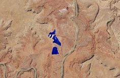 Satellite image of bright blue evaporation ponds at a potash mine in the Utah desert.