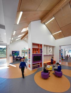 Kirkmichael Primary School / Holmes Miller perf wood ceiling colored casework kids soft seating colored floors