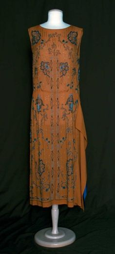 """BEADED EVENING DRESS, 1920s  Rust silk crepe w/ fanciful flowers beaded in shades of blue, 2 hip to hem panels on left side in rust crepe & blue silk, B 36"""", H 44"""", L 48"""""""