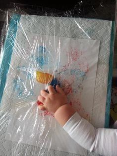 Colored ice cubes under plastic wrap. Clean and fun activity for infant hands