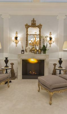 Luxurious interior with gorgeous hand-crafted Chippendale style mirror, marble fireplace mantel