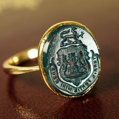 "18th Century Heraldic Intaglio Seal Ring - $ 695.00 at Butter Lane Antiques. An unusual mashup ring: a Georgian head, holding a Victorian intaglio seal carved in bloodstone. The face displays Rampant Lions and a Tower, beneath a reclined Lion - all above the latin motto: ""Turris Fortis Mihi Deus"", or ""God is a strong tower to me"". There is a very faded inscription to the back of the head that reads: ""...1739"""