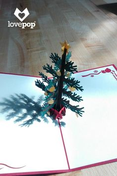 The cover of this festive pop up card shows a classic, majestic Christmas tree. Once opened the red card reveals the quintessential Christmas tree adorned with gold ornaments and topped with a lovely