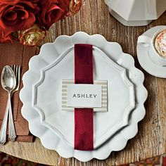 #Christmas Table Setting | This place card only looks high-end. Back a simple white card with patterned paper and then thread with sumptuous red velvet ribbon. When wrapped around white dinnerware, these crafts store finds are instantly elevated.