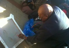 Archbishop Emeritus Desmond Tutu signs the wet cement block with an impression of his footprint.