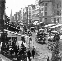 19. Broadway, New York, 1870s. Public amenities of cobblestone pavement and gas lights have been added, and buildings have grown to five and...