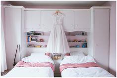 Ankle length skater style wedding dress hanging in bride's old bedroom