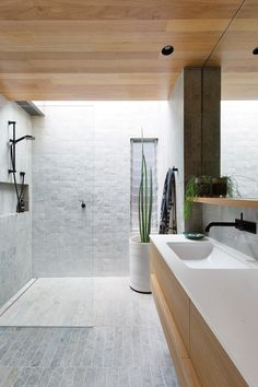"""The pair chose slim rectangular limestone tiles, laid in an offset pattern on the floor and stacked vertically on the walls. Handmade Moroccan tiles feature on the splashback and shower wall, adding to the organic feel. The cabinetry was made by All Aspects Joinery in Laminex's Sublime Teak – """"It stands up to moisture better than timber veneer,"""" says Carolyn, and Mark made the shelf and drawer handles himself from solid blackbutt"""