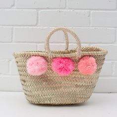 Bohemia Childs Basket With Pink Pom-poms: The Mini Market Pom Pom Basket from Bohemia, a simple French inspired basket handwoven from palm leaf with a natural sisal cord handle and 3 bright and fun colourful pom poms on each side. An adorable miniature basket ideal for kids or as statement home storage.