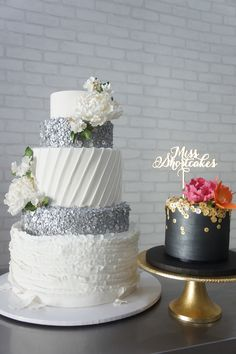 A gallery of fondant and gum paste wedding cakes from cake decorators around the world inspired by gray and silver tones.