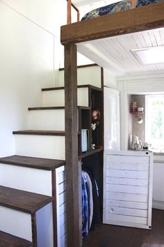 Tiny house interior with white walls, wood stairs, lofted bed, wood ceiling, wood floors, and closets in the staircase.