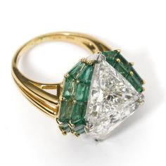 Diamond and emerald ring, Oscar Heyman & Brothers, 1993 Set with 2 triangular-shaped diamonds weighing 8.39 carats, framed by 24 baguette emeralds weighing 6.57 carats, mounted in 18 karat gold and platinum, size 6, signed OHB, numbered 28663.