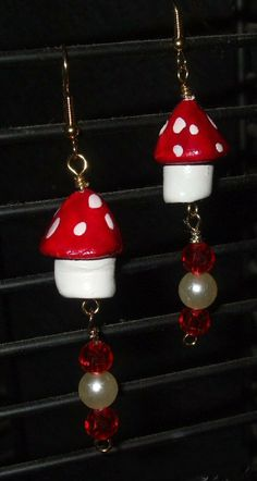 "2009-""Mushrooms Red White"" earrings. I hand made the tops and bottoms of the mushrooms using Air Dry Clay and painted them with Acrylic Red and White Paint. Then added the red crystal and faux pearl dangles at the bottom."