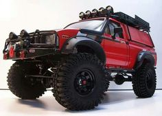 Old Red Lifted Toyota Pick-up with ARB front bumper, roof rack, and snorkel.