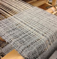 Finished one warp this afternoon and tied on to my remnants to begin this new piece. Natural cotton and black cotton warps with light grey wool wefts. It's looking very delicate. #weaving #loom #textile #fiber #cotton #wool #bridgettesegraves