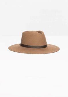 Styled from felt wool, this elegant hat is detailed with a slightly contrasting ribbon and a creased crown.