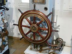 """Wielkie drewniane koło sterowe proponowane przez Marynistyka.org - ponadczasowy prezent w żeglarskim stylu, podstawowy element morskiego, marynistycznego wystroju wnętrz, ale również przedmiot o wielkiej symbolice - często ofiarowany prezesom, dyrektorom, kierownikom a nawet prezydentom jako symbol dowodzenia, trzymania steru władzy, właściwego kierowania """"okrętem i załogą"""", sterowania we właściwym kierunku, omijania raf, również życiowych i bezpiecznego prowadzenia załogi i statku do…"""