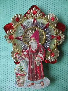 This is a vintage look victorian ornament with a vintage 1910 German postcard Santa with a red robe, enhanced with glitter, mica, gold