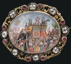 """""""A BRILLIANT DIAMOND AND RUBY BROACH DEPICTING A ROYAL PROCESSION OF AKBAR II, COMPANY SCHOOL, INDIA, CIRCA 1830 Of oval form on a gold ground, the rubies closed set, gems set amongst a scrolling vine of gold filigree encircling a miniature painting heightenend with gold leaf depicting the procession of His Majesty Akbar II (r.1806-37), surrounded by various troops, nobles and standard bearers, hook and eye clasp - 1 7/8in. (5cm.) diam. (original source: Christies)"""