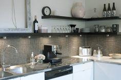 Dark open shelving, grey glass mosaic tile backsplash, plain white cabinets
