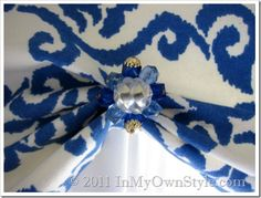 This is so clever... Simple window treatment and this is a closeup of a clip on earring used to dress it up.