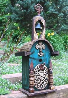 Large church birdhouse features iron scroll work and rich color to create a…