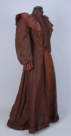 SILK ROBE de CHAMBRE, c. 1895. Brown taffeta with puffed sleeve and stand collar, striped silk bodice ruffle, ruffled cuff and back bow, interior having a button front bone cotton corset and under-skirt, stiffened hem, ribbon tie at waist possibly later.  Whitaker Auctions