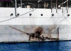 "The HMS Sussex, showing a Kamikaze ""imprint"". Probably from a Kate, fixed landing gear dive bomber."