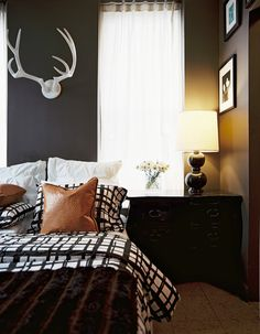 Bedroom Photo - A black lamp on a bedside table beside black-and-white bedding