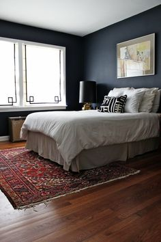 I love how airy and serene this bedroom feels, especially with having such a bold, dark color on the walls. Dark gray/grey walls, persian run, whtie bedding, striped window cover shade