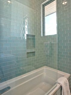 Gorgeous shower tub combo with walls and bath surround tiled in blue glass subway tile.