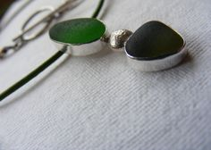 Sea glass in two green tones. A pendant on green leather with silver t-bar. Hand crafted using Devon found sea glass. Totally natural ocean tumbled sea glass.