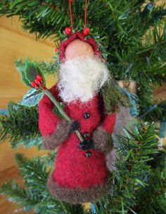 """ModerationCorner on Etsy Our woodland Santa is made from a clothespin, small wood ball, wool felt, and felt fur. He is dressed in a deep red cloak lined with dark brown fur with a sprig of greenery and berries lining his hat. He carries a """"wand"""" of holly leaves and berries. Dimensions: 2.25"""" W x 5 """" H"""