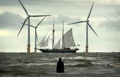 A figure from Antony Gormley's 'Another Place' welcomes one of the Tall Ships to Merseyside as it sails past the Burbo Bank wind farm on its approach to the Port of Liverpool Renewable Energy, Solar Energy, Solar Power, What Is Green, Go Green, Human Sculpture, Sculptures, Antony Gormley Another Place, Transformers