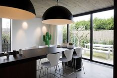 Black and white modern style kitchen island continuing with a dining table with huge lighting | Ilot cuisine et son espace déjeuner noir et blanc au style moderne
