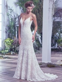 This intricately woven allover embellished lace wedding dress is highlighted with delicate beaded spaghetti straps, a plunging illusion lace neckline, and a stunning open back. These features add subtle sexy touches to this ethereal sheath wedding gown. Finished with covered buttons over zipper closure.