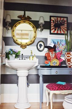 Federalist mirror, pedestal sink, striped walls, sconces... Really, this is almost spot-on perfect. Only thing I would nix is the hat on the pink bust.