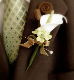 boutonneire  using a lily; looks wonderful with the colors of deep brown and mint green