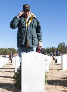A volunteer salutes a gravestone after laying his wreath at the Wreaths Across America ceremony in Canton, Ga. at Georgia National Cemetery Dec. 13, 2014. Thousands showed up to GNC to honor America's heroes. (U.S. Air Force photo/Senior Airman Daniel Phelps)
