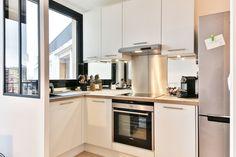 cuisine blanche ouverte avec verrière d'atelier Loft 43m² Boulogne par Laurence Garrisson