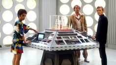Tegan Jovanka (Janet Fielding), the Fifth Doctor (Peter Davison), and Vislor Turlough (Mark Strickson) at the console of the TARDIS.