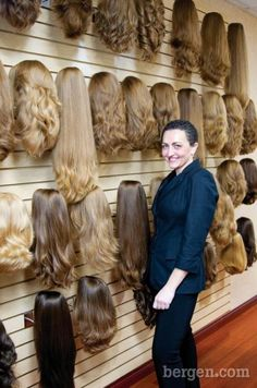 Hair Today: Shepelsky stands beside a wall of wigs in her Teaneck store, Design by Flora, which sells wigs, falls and toppers. Photo by: Anne-Marie Caruso