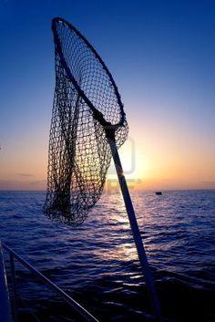 dip net in boat fishing on sunrise water horizon